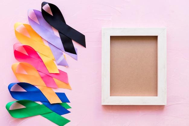 Un marco de madera vacío con cinta de conciencia colorida sobre fondo rosa