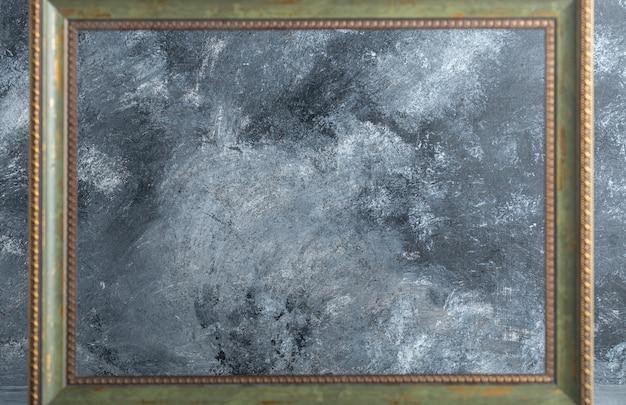 Marco de madera vacío sobre mármol.