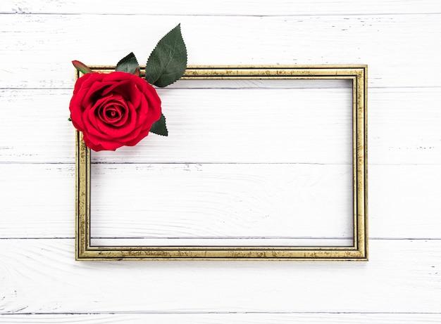 Marco de madera vintage dorado y una rosa roja