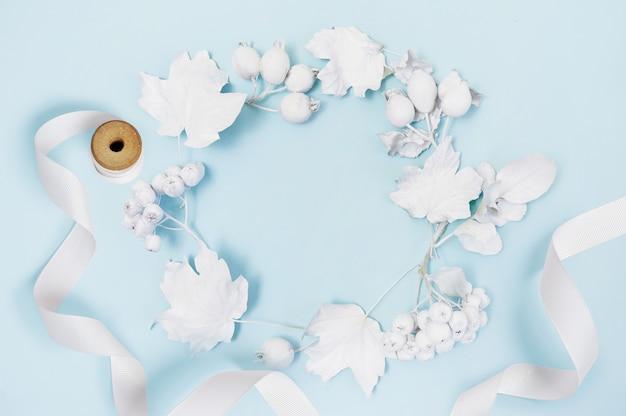 Marco de maqueta con calabaza blanca, cinta, bayas y hojas