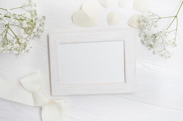 Marco de la maqueta con flores y arco tarjeta de felicitación
