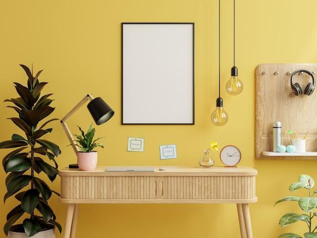 Marco de la maqueta en la mesa de trabajo en el interior de la sala de estar en la pared amarilla vacía background.3d rendering