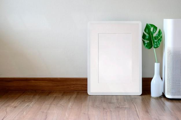Marco de la maqueta con planta de interior sobre piso de madera, espacio de copia para exhibición de productos