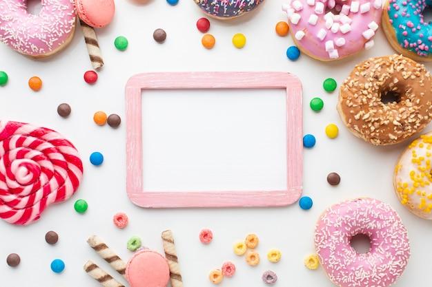 Marco de maqueta rodeado de dulces
