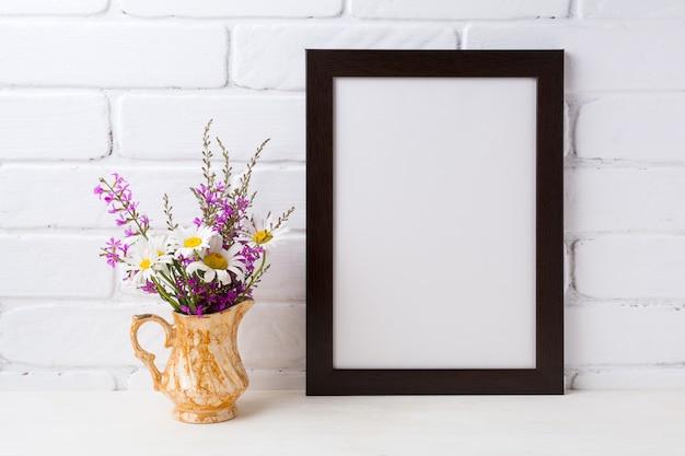 Marco marrón negro con manzanilla y flores de color púrpura en jarra dorada