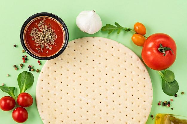 Marco de masa e ingredientes para pizza