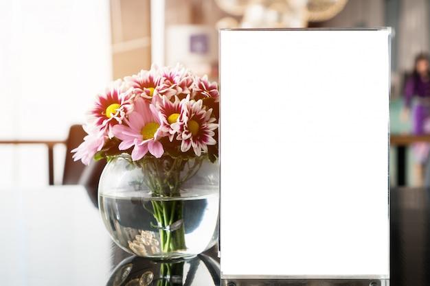 Marco de menú en blanco blanco en el restaurante cafetería con flores de plantas. soporte de hojas de folletos, carpa de papel, tarjeta en la mesa, cafetería
