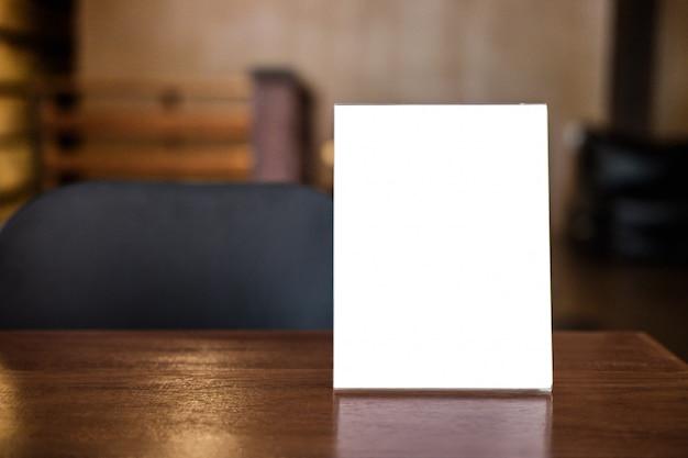 Marco de menú en blanco en la mesa en la cafetería soporte para texto de pantalla