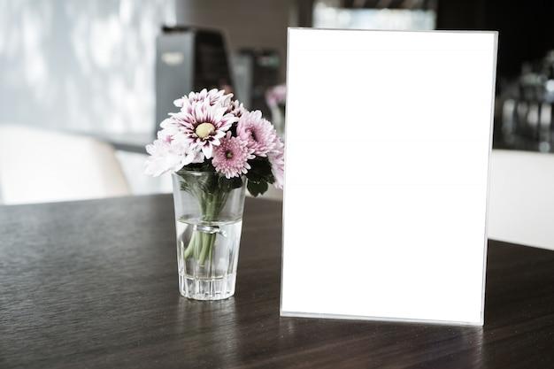 Marco de menú en blanco en el restaurante con flores de plantas