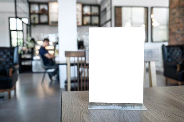 Marco de menú de maqueta de pantalla en blanco de pie sobre la mesa de madera en el fondo