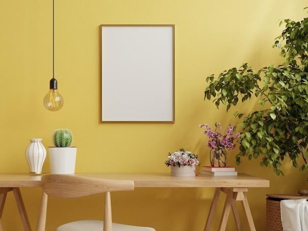 Marco en la mesa de trabajo en el interior de la sala de estar en la pared amarilla vacía