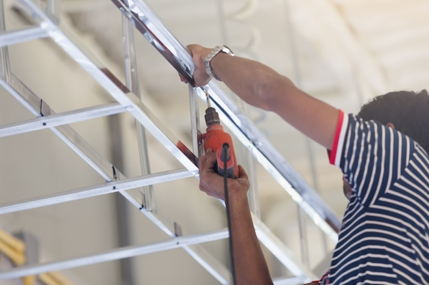 Marco de metal del techo de trabajador de construcción con destornillador para techo de placa de yeso de construcción interior