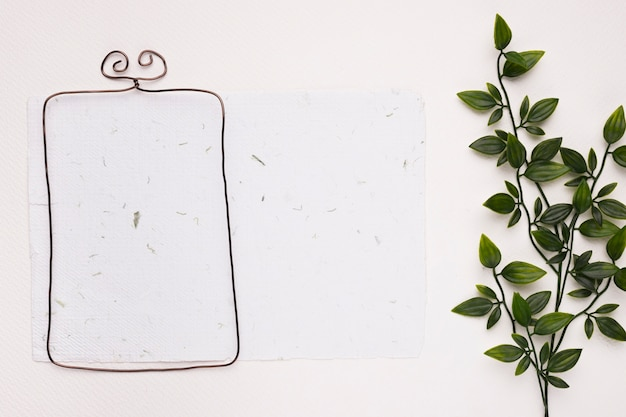 Marco metálico sobre papel con textura con hojas artificiales verdes sobre fondo blanco.