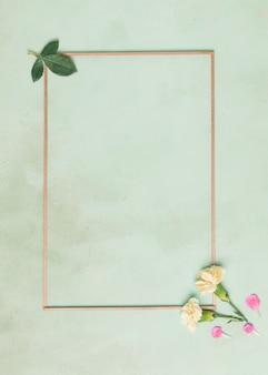 Marco minimalista con flores de clavel y hojas sobre fondo azul.