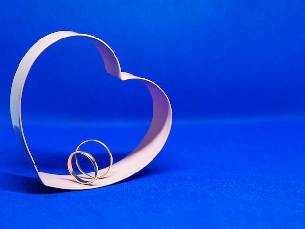 Marco de molde de galleta en forma de corazón. en el centro anillos de boda. fondo azul, aislado, copia espacio para mensaje. concepto de san valentín declaración de amor.