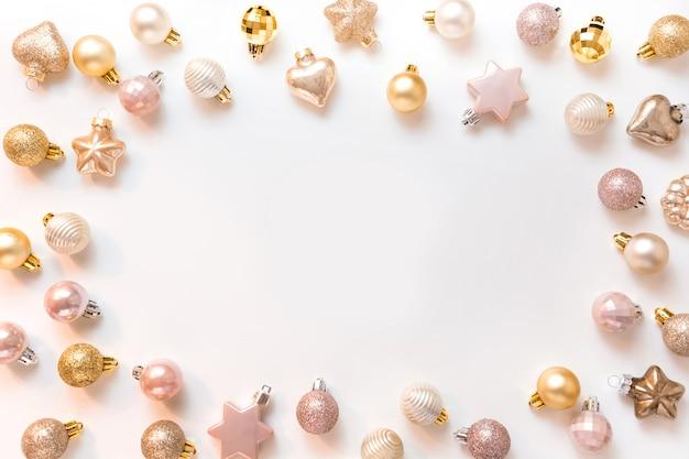 Marco de navidad de bolas doradas y rosadas en blanco neutro. vista superior. frontera de navidad para los deseos. tarjeta de felicitación.
