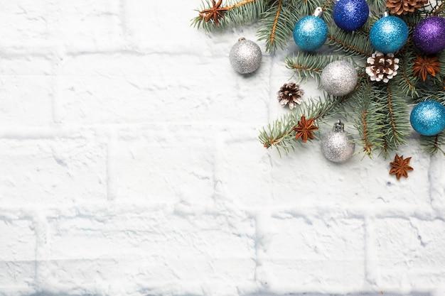 Marco de navidad hecho de abeto, decoraciones para árboles de navidad en plata y azul sobre un fondo de ladrillo claro. copia espacio endecha plana.