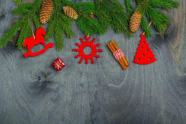 Marco de navidad de ramas de abeto y decoración de juguetes hechos a mano sobre un fondo oscuro de la madera. navidad, vacaciones de invierno, año nuevo concepto. vista superior, plano, copia espacio para texto