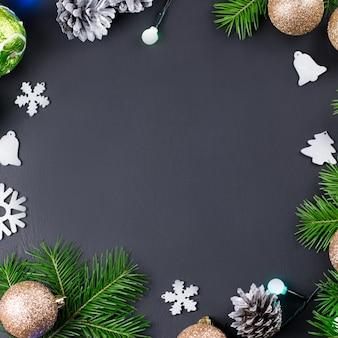 Marco de navidad con ramas de abeto, luces, adornos dorados y plateados en madera negra. copia espacio
