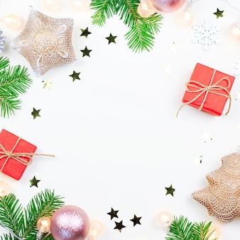 Marco de navidad con ramas de abeto, luces de navidad, adornos de color rosa y beige sobre blanco
