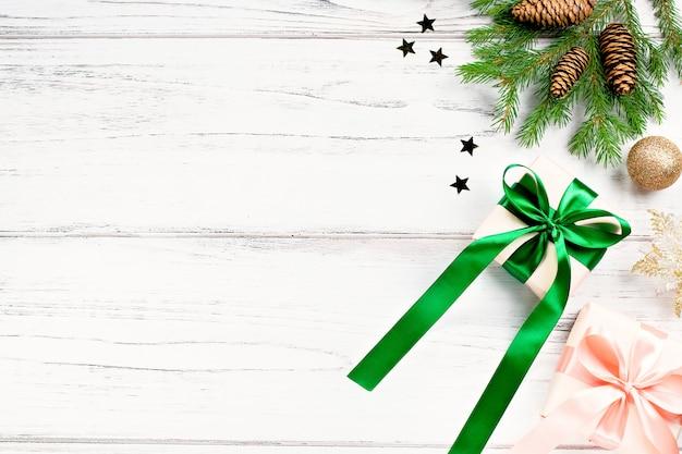 Marco de navidad con ramas de abeto, regalos envueltos en colores rosa y verde, confeti. navidad plana, copia espacio