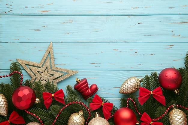 Marco de navidad - ramas de árboles con adornos rojos y dorados, estrellas, copos de nieve sobre fondo azul. vista superior