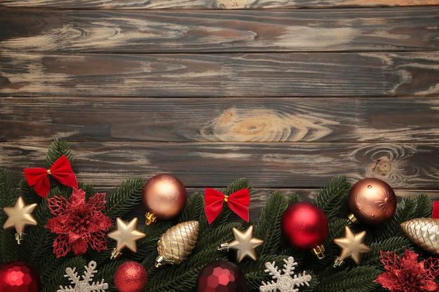 Marco de navidad - ramas de árboles con adornos rojos y dorados, estrellas, copos de nieve sobre fondo marrón. vista superior
