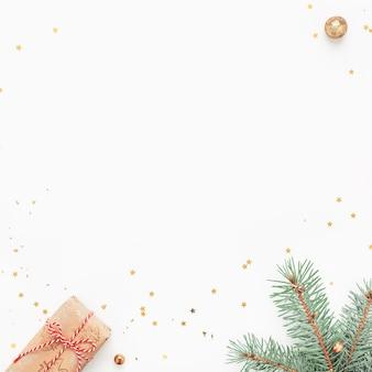 Marco de navidad de ramas verdes, regalos, adornos de oro sobre fondo blanco.