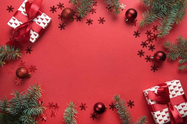 Marco de navidad con regalos, bolas, abeto sobre fondo rojo. tarjeta de felicitación. feliz año nuevo.