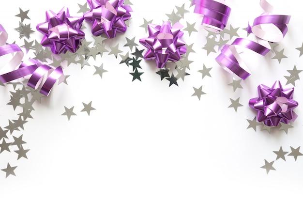 Marco navideño de plata y rosa pastel decoración, bolas, oropel y estrellas sobre fondo blanco.