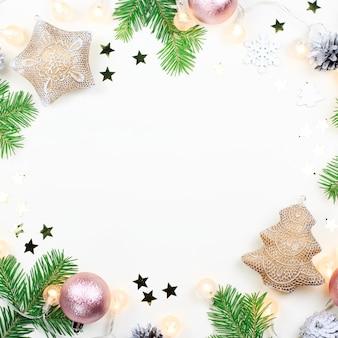 Marco navideño con ramas de abeto, luces navideñas, adornos rosas y beige, adornos plateados