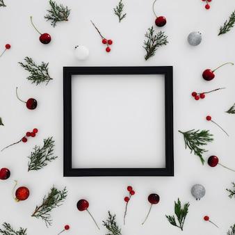 Marco negro con patrones hechos con hojas de pino y bolas decorativas de navidad.