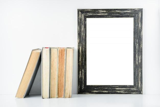 Marco negro vacío y libros viejos en un fondo blanco.