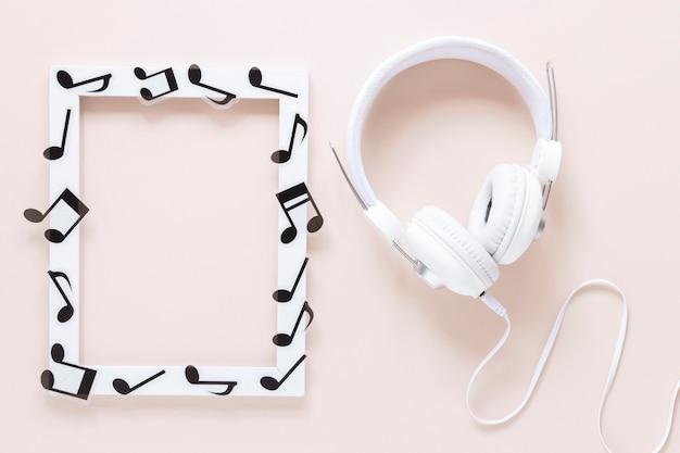 Marco de notas musicales de vista superior con auriculares