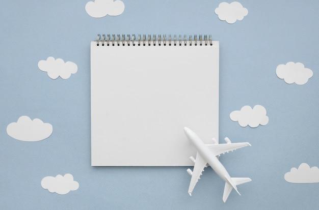 Marco de nubes con avión y cuaderno
