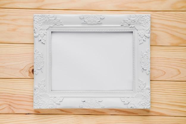 Marco ornamental blanco con fondo de madera