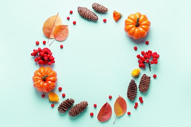 Marco de otoño con hojas, bayas de serbal, calabazas naranjas, piñas sobre fondo pastel