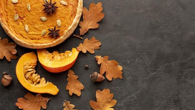 Marco de otoño vista superior con pastel y calabaza