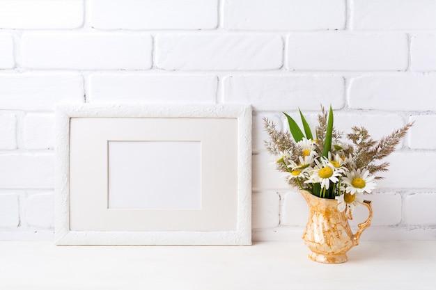 Marco de paisaje blanco con manzanilla y hierba en florero dorado