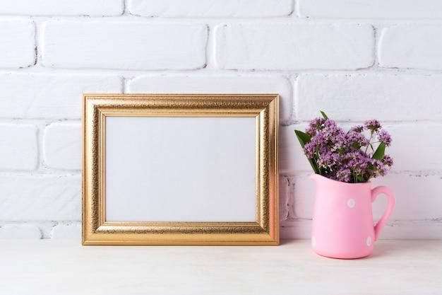 Marco de paisaje dorado con flores de color púrpura en la jarra rústica rosa