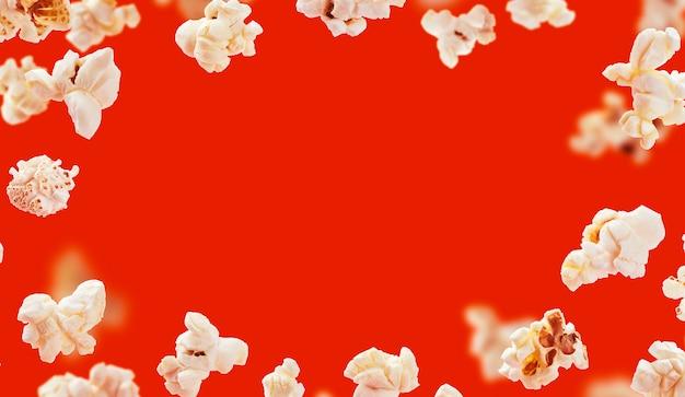 Marco de palomitas de maíz, palomitas de maíz volando aislado sobre fondo rojo con espacio de copia