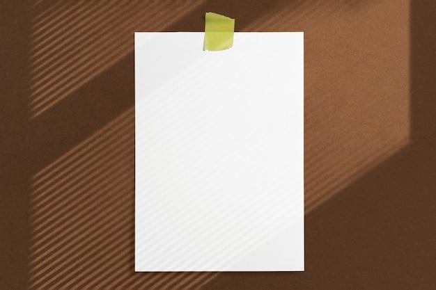 Marco de papel en blanco de tamaño 10 x 15 pegado con cinta adhesiva a la pared con textura marrón con suaves sombras de ventana de adobe