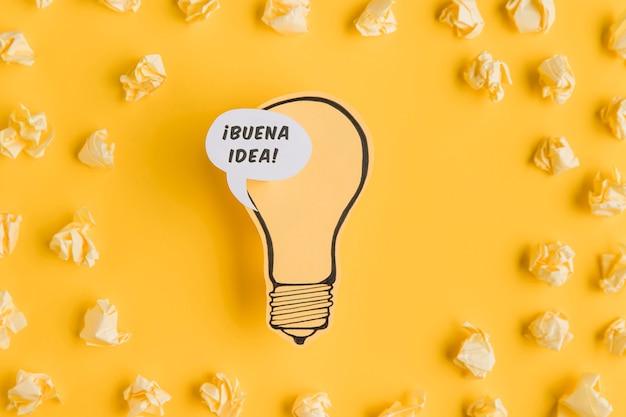 Marco de papel motolite con bombilla sobre fondo amarillo