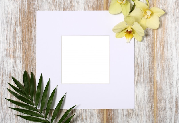 Marco de papel con orquídeas amarillas y hojas de palma