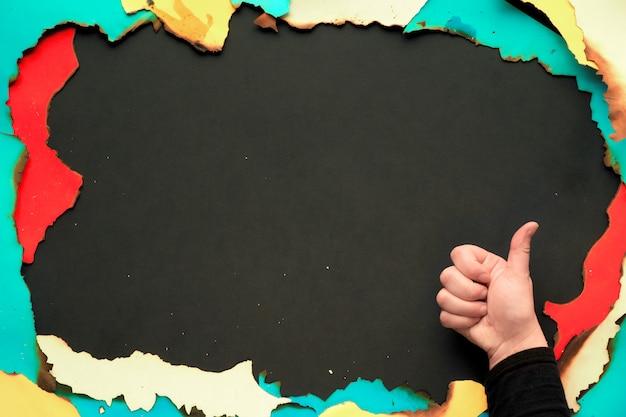 Marco de papel quemado con papel blanco, rojo, amarillo y turquesa con bordes quemados, pared creativa de papel negro, mano en la manga negra que muestra el signo ok, espacio de copia.