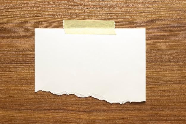 Marco de papel rasgado en blanco pegado con cinta adhesiva a la pared con textura de madera