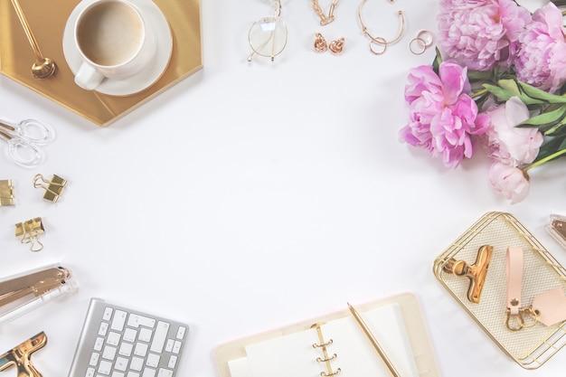Marco de papelería de oro sobre un fondo blanco. diario, calculadora, taza de café, engrapadora, perforadora, bolígrafo, vasos y teclado.