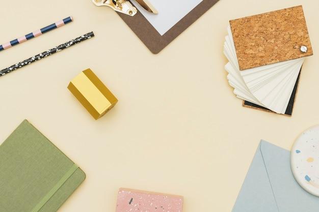 Marco de papelería pastel sobre una mesa beige