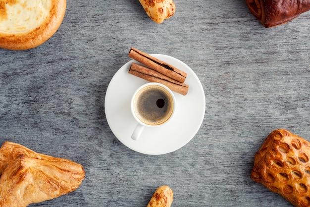 Un marco de pasteles y croissants alrededor de una taza de café