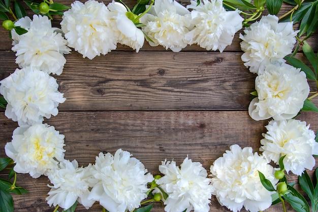 Marco de peonía blanca sobre fondo de madera